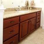 Red cherry vanity with a granite counter top and an under-mount sink