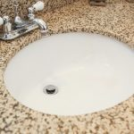 Granite countertop with undermount sink with a Moen Eva faucet with chrome finish.