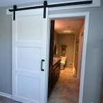 We added a sliding white barn door with wrought iron trim.