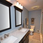 The custom vanity has a double bowl and espresso-stained with a granite counter top.