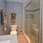 """The 12' shower features faux marble tile from floor to ceiling tile with 4"""" feature strip and extra-wide recessed niche."""