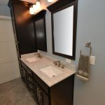 Two wood-framed mirrors and full-length linen tower match the vanity with 2 sets of 3 vanity lights.