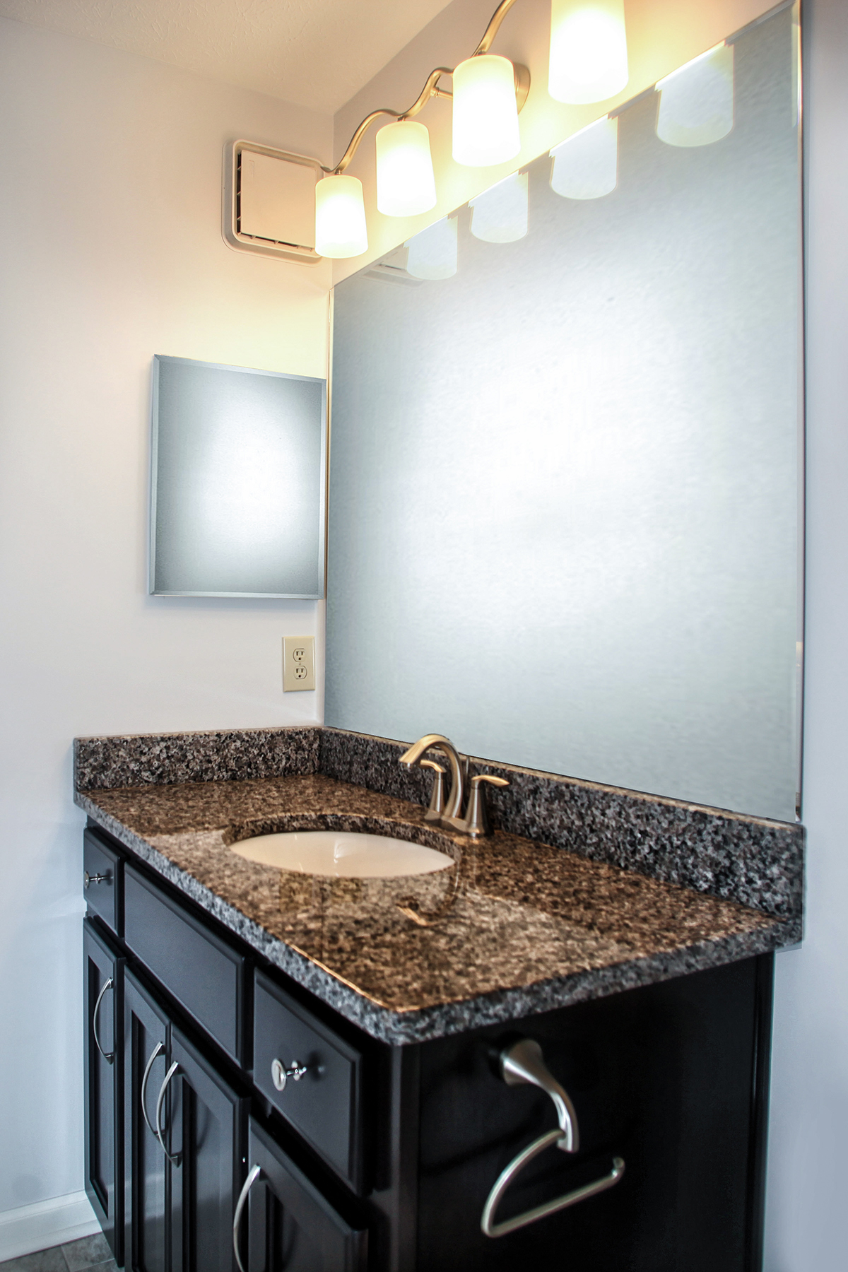 The Custom Made Wood Stained Vanity Features A Granite Countertop And Mirrored Medicine