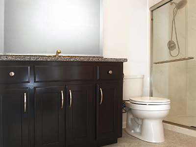 The custom-made, wood-stained vanity features a granite countertop.