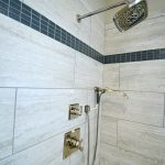 "The shower has a 12"" x 24"" tile with 4"" feature strip, polished nickel shower/faucet hand held."
