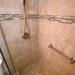 Shower with floor to ceiling tile, mosaic strip, hand-held combo shower heard